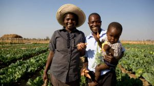 Zimbabwean family in front of crops