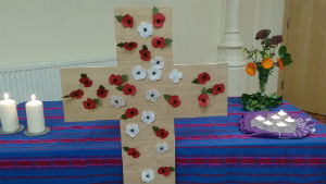 red and white poppies on a cross