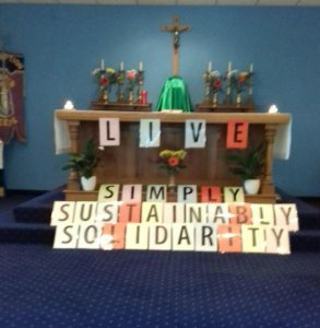 the words simply, sustainably and solidarity in front of a church altar