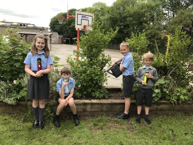 children in front of plants in garden