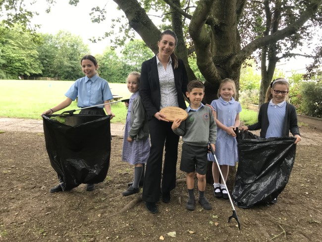 children clearing litter and holding plaque